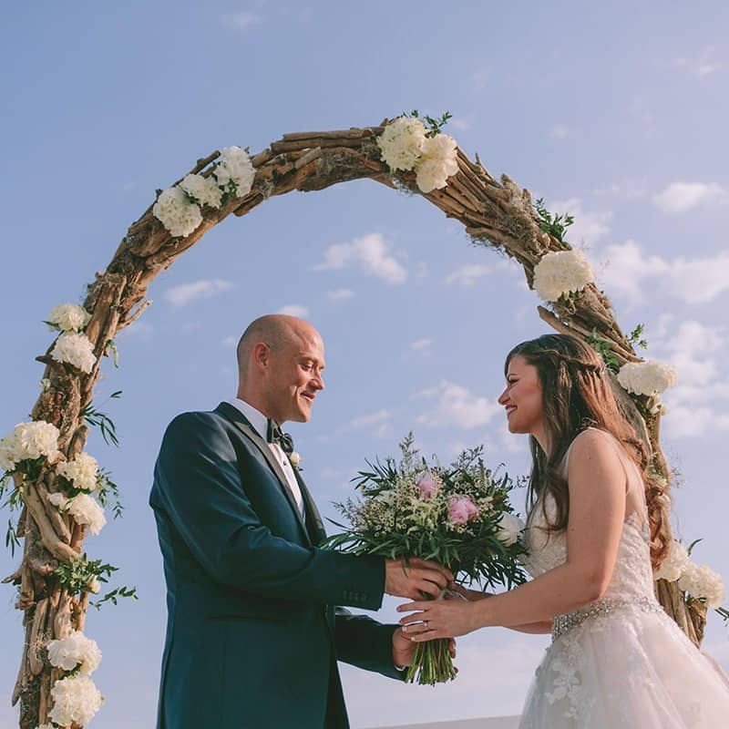 Groom giving his bride the bridal bouquet before their wedding ceremony.