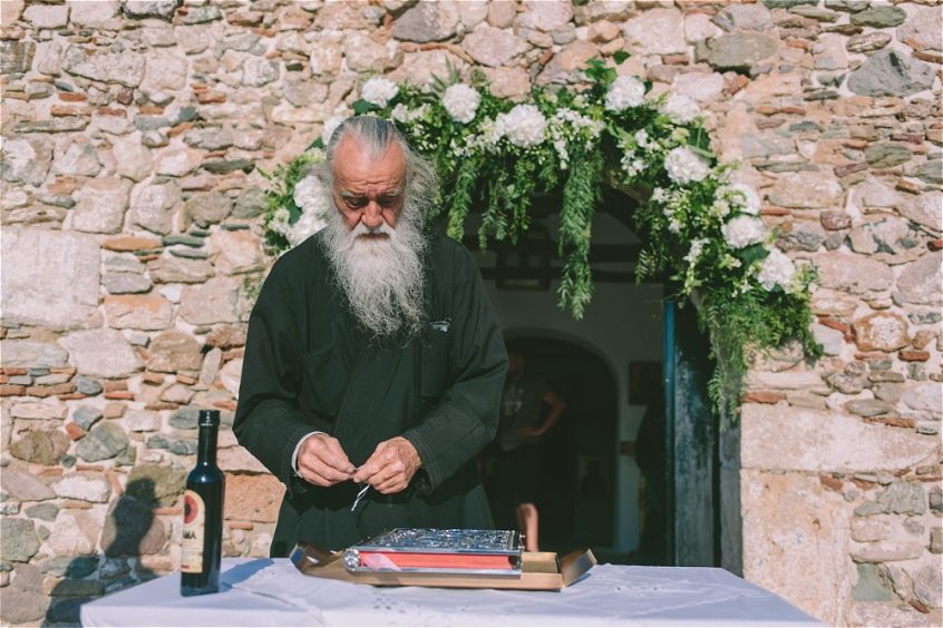 Priest in front of a Greek stone church