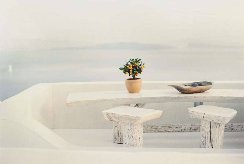Santorini island view of balcony, with stone chairs and tables and ceramic pot with plant on top