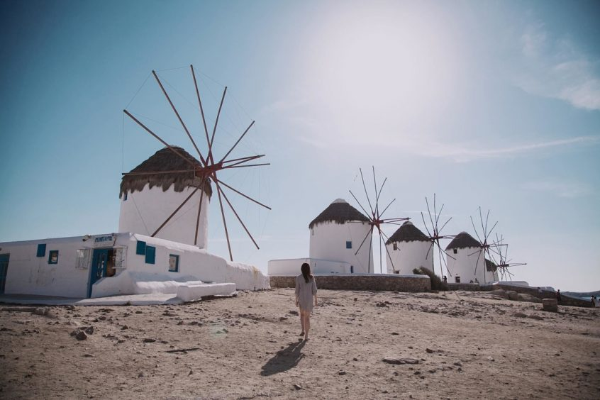 Woman walking in front of Mykonos windmillsdding in Greece, in front of the beach with chairs and the wedding aisle