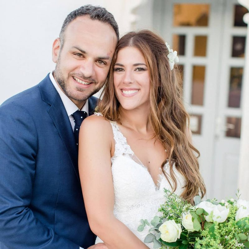Beautiful young couple looking at the camera, groom with blue suit and polka dot neck tie and bride with mermaid hairdo and white flowers on the day of the wedding