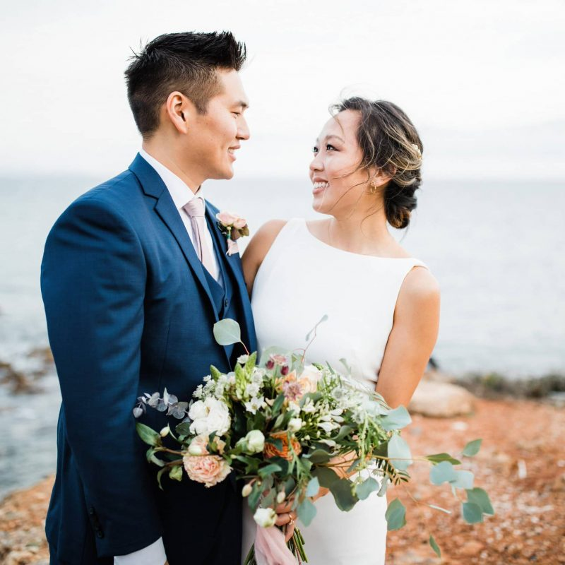 Bride with minimal wedding dress and organic flowers looking at her groom.