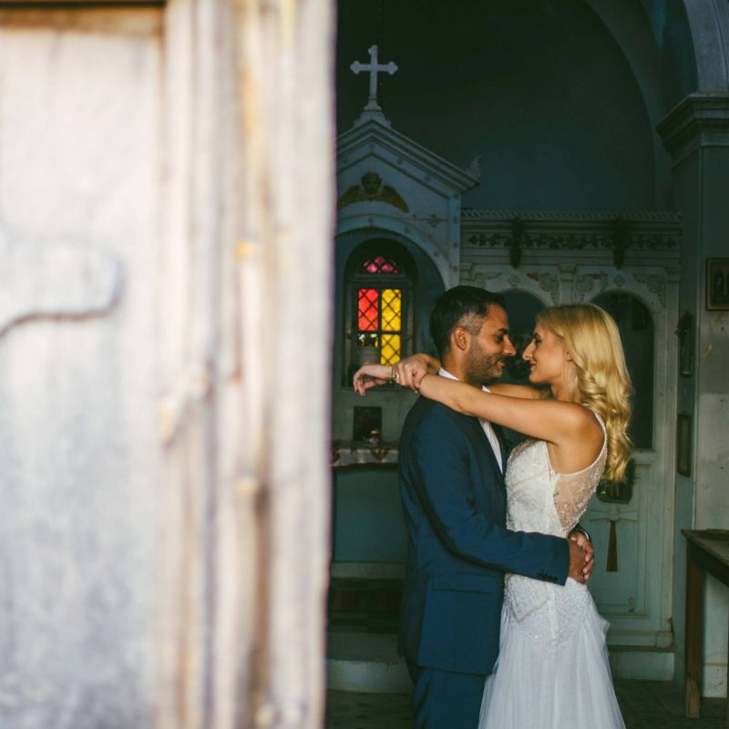 White stories events wedding: Couple in love bride and groom looking at each others eyes hugging in a church after their wedding.