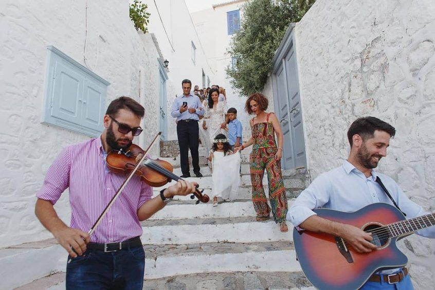 wedding in hydra couple walking down stairs with band